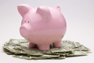 Pink Piggy Bank On Top Of A Pile Of One Dollar Bills